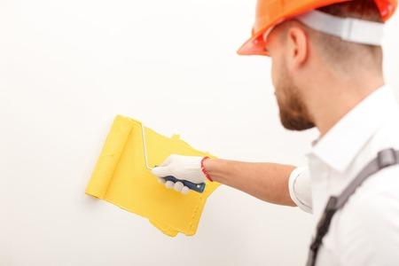 alba�il: Constructor joven H�bil est� pintando la pared. �l est� de pie y sosteniendo un rodillo. El hombre lleva un hardhead naranja