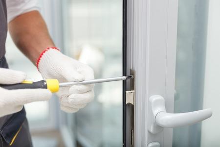Close-up van de handen van de jonge timmerman met een schroevendraaier en de vaststelling van het slot van de deur. De man staat in werkkleding Stockfoto