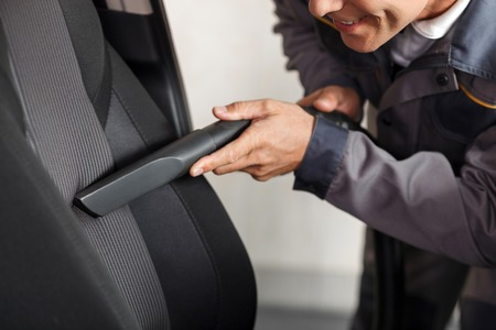 seat: Close up of cheerful car repair shop worker is cleaning the interior of the car. He is holding a vacuum cleaner and touching it to the seat. The man is smiling