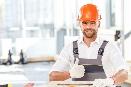 materiales de construccion: Carpintero joven hermoso que est� haciendo mediciones de tablero de madera. �l est� sentado en la mesa y la celebraci�n de un gobernante. El hombre est� mirando hacia adelante y sonr�e. �l est� dando el pulgar arriba