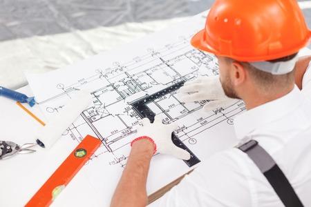 albañil: joven constructor experimentado está trabajando en nuevo proyecto. Él está mirando a croquis de construcción con seriedad. El hombre está sentado en la mesa y la celebración de un gobernante