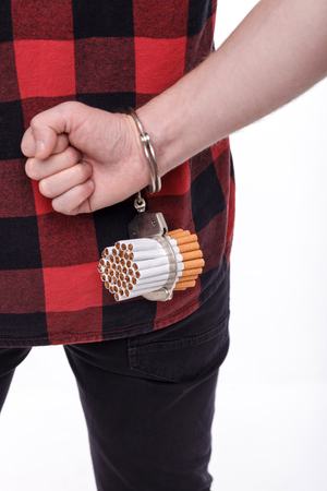 manacles: I am a prisoner of smoking. Close up of male hand attached to cigarettes with manacles