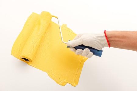 pintor de casas: Cerca de la mano del pintor profesional que sostiene un rodillo y pintura de la pared