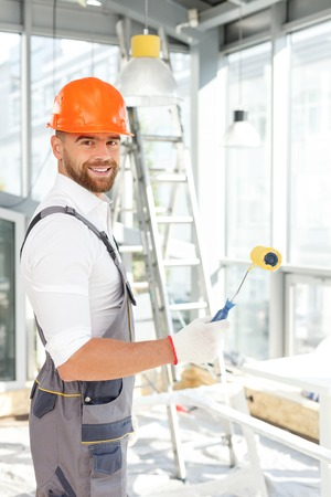 alba�il: constructor de sexo masculino atractivo est� listo para pintar las paredes. �l est� de pie y sosteniendo un rodillo. El hombre est� mirando a la c�mara y sonriendo