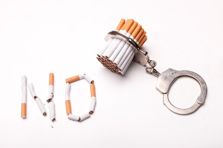 manacles: No smoking. Close up of cigarettes attached to manacles
