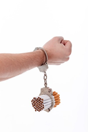 manacles: Smoking is my punishment. Close up of arm of man attached to cigarettes with handcuffs
