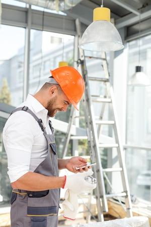 constructor: constructor joven alegre es la celebración de un teléfono móvil y mensajería. Él está de pie y sonriente. El hombre lleva ropa de trabajo y con un casco