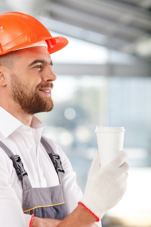 builder: Attractive young builder is drinking coffee and resting. He is standing and holding a cup. The man is smiling with pleasure Stock Photo
