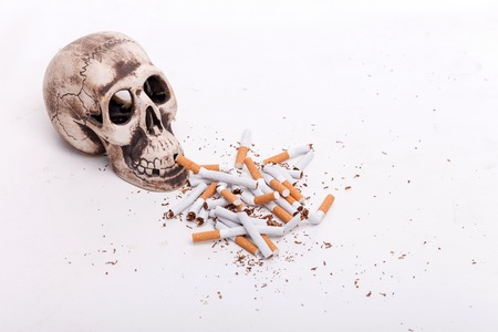 near death: Smoking is death. Close up of heap of broken cigarettes near skull. Isolated Stock Photo