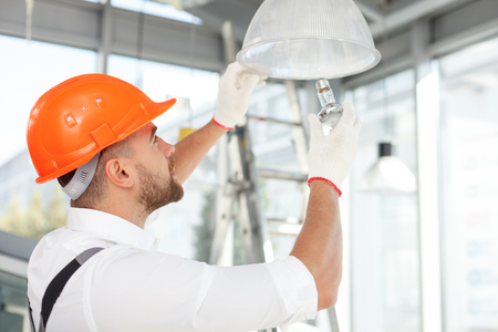 electric material: Handsome builder is screwing an electric light bulb into a fixture. He is standing and looking up with concentration