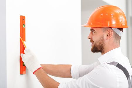 constructor: Constructor joven alegre que está midiendo la pared del edificio. Él es la celebración de una regla y dibujar la línea. El hombre está de pie y sonriente