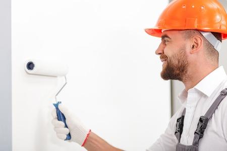 alba�il: Constructor joven hermoso que est� pintando las paredes con un rodillo. �l est� de pie y sonriente