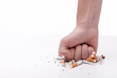 Aufhören zu rauchen. Close up der männlichen Hand brechen Zigaretten mit der Faust. Isoliert und Kopie Platz in der linken Seite