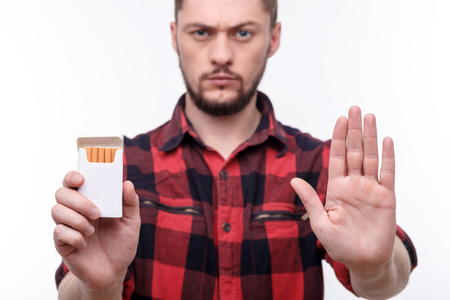 Stop smoking. Attractive young man is holding a pack of cigarettes. He is standing and making refusing gesture. The man is looking at camera seriously Reklamní fotografie