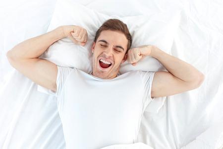 Vrolijke jonge man wordt wakker na het slapen in de ochtend. Hij wordt gieren en strekt zijn armen omhoog. Zijn ogen zijn gesloten met ontspanning. Hij ligt in het bed Stockfoto