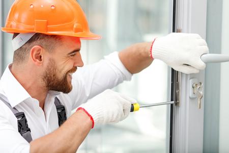 Aantrekkelijke jonge bouwer installeert slot in de deur. Hij houdt een schroevendraaier en knielen. De man lacht. Hij draagt een helm