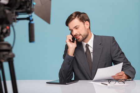 newsman: Cheerful young tv newscaster is talking on the mobile phone and smiling. He is sitting at desk in studio in front of the camera. The man is holding documents. Isolated on blue background Stock Photo