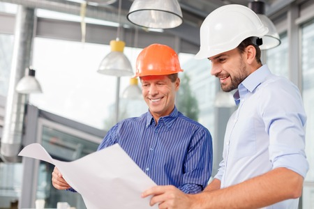 Professional two engineers are planning the construction. They are holding a blueprint and looking at it with inspiration. The men are standing and smiling