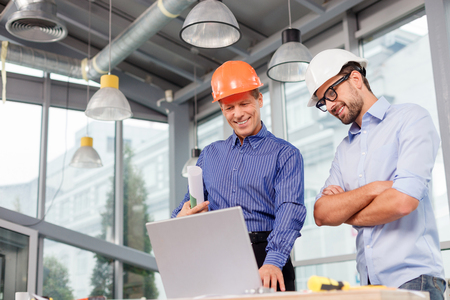 Professional two engineers are discussing the new project. They are using a laptop and smiling. The senior man is standing and holding the blueprint. Copy space in left side