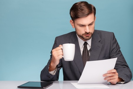 tv reporter: Handsome young tv reporter is preparing for speech at studio. He is sitting at the table and reading documents with interest. The man is drinking coffee and holding papers. Isolated on blue background