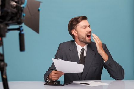 yawing: Professional male tv reporter is very tired. He is sitting at desk and yawing with closed eyes. The man is holding documents at studio. Isolated on blue background Stock Photo
