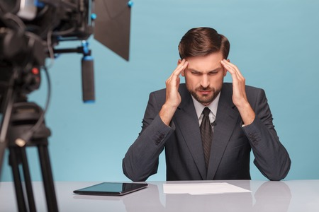 tv reporter: Skillful young tv reporter has a headache. He is sitting at desk in studio and touching his temples with disappointment. Focus on camera. Isolated on blue background