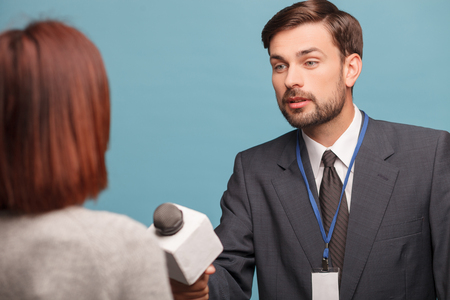 tv reporter: Cheerful male tv reporter is asking the woman to give his the interview. He is holding a microphone and stretching in forward. The man is standing and listening attentively. Isolated Stock Photo