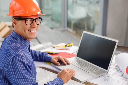 notebook: Experienced senior architect is designing a new construction. He is sitting at the desk and using a laptop. The man is looking at camera and smiling