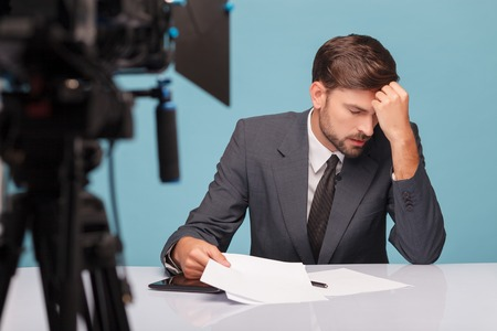 tv reporter: Attractive young tv reporter feels pain in head. He is sitting at desk in studio and touching his forehead with frustration. His tired eyes are closed. Focus on camera and isolated on blue background Stock Photo