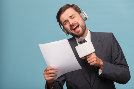 cantando: joven apuesto presentador est� cantando en el micr�fono con pasi�n. �l est� de pie y escuchar m�sica de los auriculares. El hombre es la celebraci�n y la lectura de peri�dicos. Aislado en el fondo azul