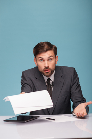 newsman: Cheerful male tv reporter is looking at camera with shock. He is holding papers and raising in with question. The man is sitting at a desk near the tablet. Isolated on blue background