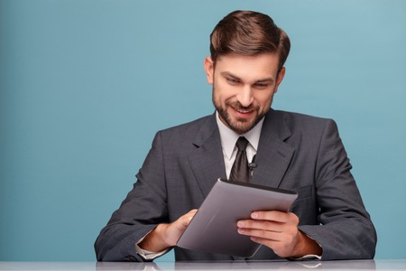 newsman: Attractive young anchorman is using a tablet. He is sitting at desk and smiling. Isolated on blue background