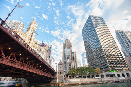 Beautiful panorama of bridge with American flags and river in Chicago. There are many outstanding buildings on background Фото со стока