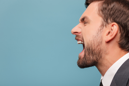 side  profile: Close up of face of man shouting with anger. He is standing in profile. Isolated on blue background. Copy space in left side
