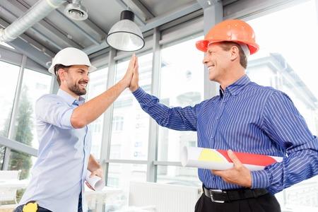 Goed gedaan werk. Ervaren twee ingenieurs geven high five. Zij staan en lachen. De mannen in helmen houden blauwdruk van de bouw