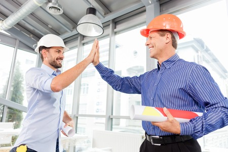 high five: Well done work. Experienced two engineers are giving high five. They are standing and laughing. The men in helmets are holding blueprint of construction