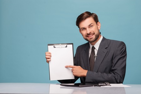 tv reporter: Handsome young tv reporter is sitting at table in studio. He is holding a folder of document and pointing his finger at it. The man is smiling. Isolated on blue background and copy space in left side
