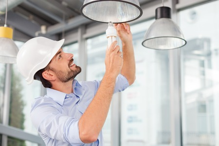 twisting: Handsome young builder is twisting the light bulb in. The man is looking up and smiling. He is standing in a white helmet Stock Photo
