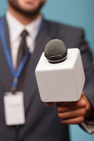 tv reporter: Close up of hand of young tv reporter standing and interviewing someone. He is holding a microphone and stretching his arm forward. Focus on the equipment