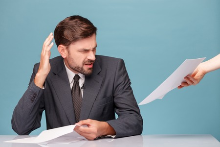 negatively: Professional young male newscaster is refusing to read the documents. He is looking at it with frustration and gesturing negatively. The man is sitting at desk in studio. Isolated on blue background Stock Photo
