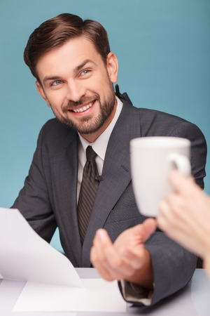 tv reporter: Cheerful male tv reporter is studying documents before reporting. He is sitting at table and smiling. The female hand of assistant is giving him a cup of tea. Isolated