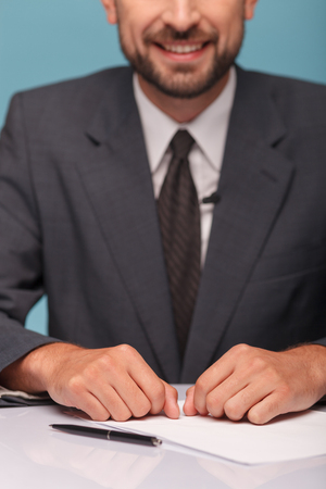 tv reporter: Close up of young tv reporter telling some good news. He is sitting at the desk and smiling Stock Photo