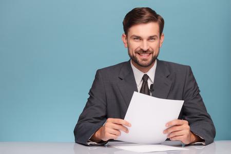 매력적인 젊은 텔레비젼 뉴스 해설자는 뉴스를보고하고있다. 그는 스튜디오에서 책상에 앉아있다. 남자는 카메라를보고 웃 고있다. 왼쪽에 파란색 배