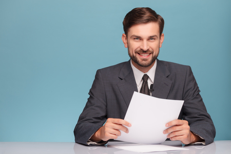 reportero: Atractiva joven locutor de televisión está informando de noticias. Él está sentado en el escritorio en un estudio. El hombre está mirando a la cámara y sonriendo. Aislado en el fondo azul y copia espacio en el lado izquierdo Foto de archivo