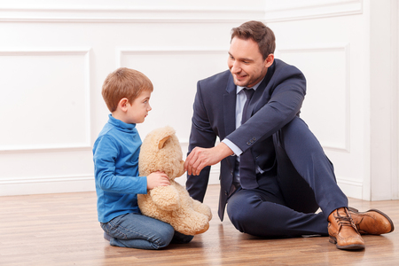 calm down: Cheerful small child is sitting on flooring near his father. He is holding a Teddy bear and looking at the busy man with abuse. The man is trying to calm down his son and smiling Archivio Fotografico