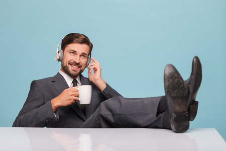 musing: Attractive businessman is drinking coffee and relaxing. He is sitting and putting his legs on the table. The man is listening to musing from headphones and smiling. Isolated on blue background