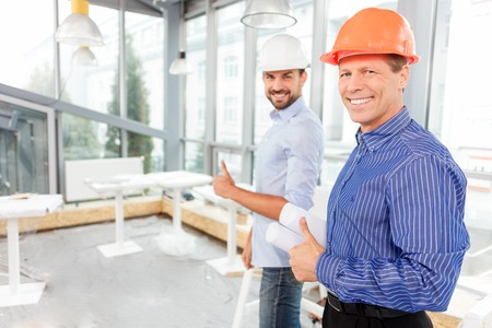 two thumbs up: Skillful two architects are giving thumbs up with happiness. They are standing and smiling. The senior man is holding blueprints. Copy space in left side