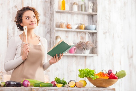 Cheerful young woman is cooking in the kitchen with joy. She is standing and holding a book of recipe. The lady is touching a wood spoon to her face and dreaming. She is smiling