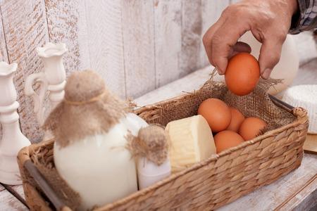 tomando refresco: Cerca de la mano del viejo que lleva un huevo de la cesta. Hay botellas de leche, el queso y los huevos en la cesta en la tabla Foto de archivo
