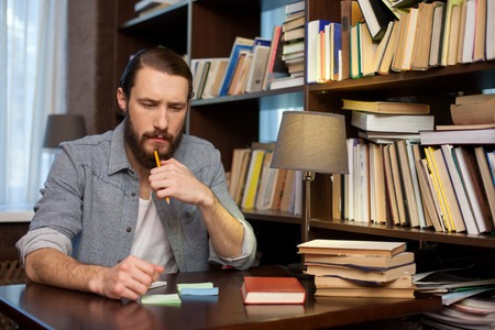 seriousness: Handsome young man is studying with books at the library. He is sitting at the desk and thinking with seriousness. The student is touching a pencil to his beard